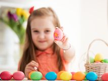 Young girl showing drawing on an egg. Young girl showing a hand-made egg with a chicken drawing on it. Easter traditions Royalty Free Stock Photos