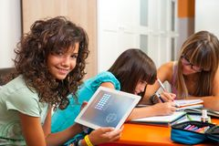 Young girl showing homework on tablet indoors. Royalty Free Stock Image