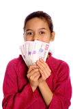 A young girl showing off a bunch of  currency. Isolated on white Royalty Free Stock Photography
