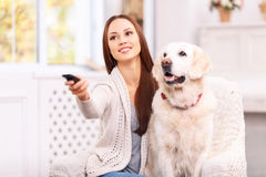 Young girl showing something to her dog on TV Royalty Free Stock Image