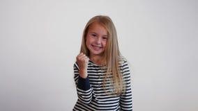 Young girl showing winner gesture. Success concept. Studio shot stock video