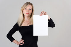 Young girl shows a blank sheet of paper Royalty Free Stock Photos
