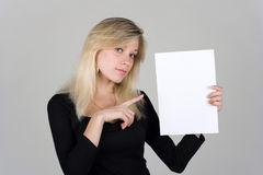 Young girl shows a blank sheet of paper Stock Image