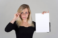 Young girl shows a blank sheet of paper Stock Photos