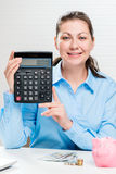 Young girl shows on the calculator the earned. Amount of money Royalty Free Stock Photo