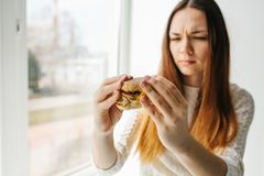 A young girl shows that she does not like a burger. Conceptual image of refusal from unhealthy eating. Royalty Free Stock Image
