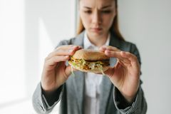 A young girl shows that she does not like a burger. Conceptual image of refusal from unhealthy eating. Stock Photos