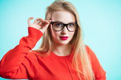 A young girl shows the fashionable glasses. Beautiful woman with red lips and dress on blue background. Ophthalmology Royalty Free Stock Images