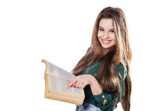 Young girl shows a finger in the book on the isolate. Is reading. Smiles Stock Photo