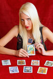 Young girl shows the future. Young woman interprets the future Tarot cards in their hands Stock Images