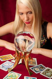 Young girl shows the future. Young woman from the future signs tarot cards and crystal ball Royalty Free Stock Photography