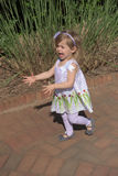 A young girl shows happiness as she explores the sights at a public garden Royalty Free Stock Image