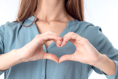 Young girl shows a heart-shaped gesture close-up Royalty Free Stock Photo