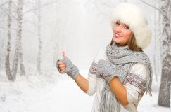 Young girl shows ok gesture on snowy forest Royalty Free Stock Photo
