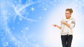 Young girl shows pointing gesture on winter background Royalty Free Stock Images