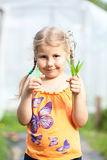 Young girl shows scissors and green plant in hands Royalty Free Stock Photography