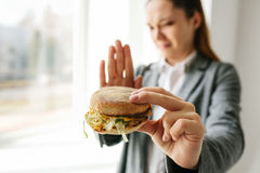 A young girl shows a sign by hand signifying there is no burger. Conceptual image of refusal from unhealthy eating. Stock Image