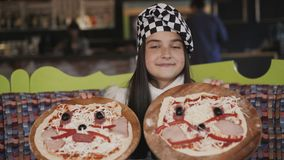 The young girl shows two pizzas at camera. 4K stock footage