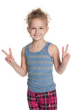 Young girl shows a victory sign Royalty Free Stock Image