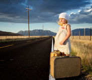 Young girl on side of road with suitcases Royalty Free Stock Photo