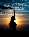 Young girl silhouette with shawl on background of beautiful cloudy blue sky with yellow golden sunset Stock Photos