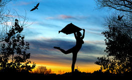 Young girl silhouette with shawl dancing on blue and golden cloudy sunset Stock Photo