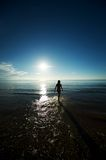 Young girl silhouette walking in the sea Royalty Free Stock Images
