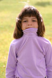 Young Girl Silly. An adorable young Latin American girl in the 5-8 year old age range. She is wearing a pink purple turtleneck and has brown hair glowing in the Royalty Free Stock Photos