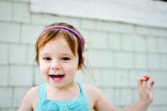 Young girl with silly face. Young 3 year old girl making silly face with hand up in the air Stock Images