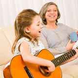 Young girl sing play guitar to grandmother. Young girl granddaughter sing play guitar to grandmother smile Royalty Free Stock Photos