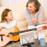 Young girl sing play guitar to grandmother. Young girl granddaughter sing play guitar to grandmother smile Stock Photography
