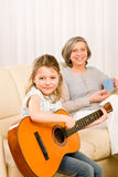 Young girl sing play guitar to grandmother. Young girl granddaughter sing play guitar to grandmother smile Stock Photos