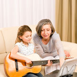 Young girl sing play guitar to grandmother. Young girl granddaughter sing play guitar to grandmother smile Stock Images