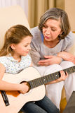 Young girl sing play guitar to grandmother. Young girl granddaughter sing play guitar to grandmother smile Stock Photo