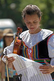Young girl, singer at violin from Poland in traditional costume Royalty Free Stock Image
