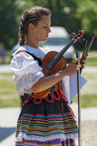 Young girl, singer at violin from Poland in traditional costume Stock Photos