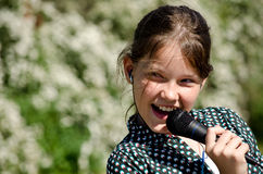 Young girl singing. Karaoke into microphone stock images