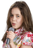 Young girl singing. Pretty young girl holding a microphone and singing stock photography