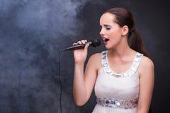 The young girl singing in karaoke club Stock Image