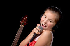 A young girl singing with a microphone Royalty Free Stock Images