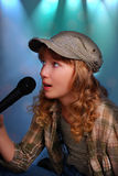 Young girl singing with a microphone on the stage Royalty Free Stock Photo