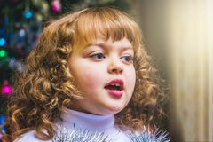 Young girl singing on New Year`s Eve on blurry background Christ. Mas trees with ornaments stock images