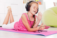 Young girl singing a tune listening to music on her phone. Lying on the floor at home stock photography
