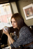 Young girl sipping coffee Stock Images