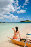 Young girl sit on boat on white beach Royalty Free Stock Photos