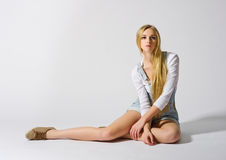 Young girl sit on the floor on grey. Background Royalty Free Stock Images