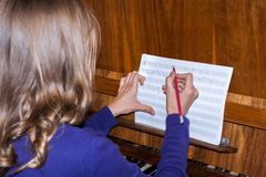 Young girl is siting at piano and writing musical notes. Rear View. Selective focus stock photos