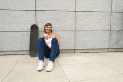 Young girl siting on skateboard in the city. Stock Photography