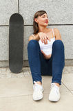 Young girl siting on skateboard in the city. Royalty Free Stock Photos