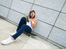 Young girl siting on skateboard in the cty with tablet. Stock Photo